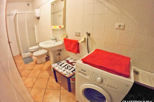 Bagno con cabina doccia e lavatrice