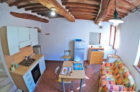 Cucina dotata di forno, frigorifero, lavandino di pietra e ripostiglio con lavatrice